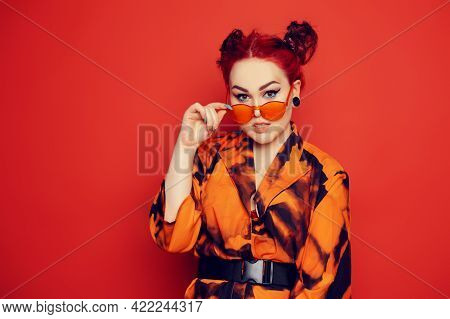 Cute Girl On A Red Background. Red Hair And Tunnels In The Ears, Red Dress And Lips. Anime Poses. A