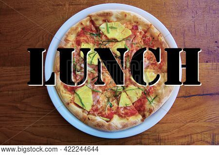 Hawaiian Pizza. A Ham and Pineapple Pizza on a white plate on a wooden table for lunch. Pizza is enjoyed world wide by hungry people. Pizza Poster with the word LUNCH.