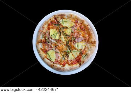 Hawaiian Pizza. A Ham and Pineapple Pizza on a white plate on a wooden table for lunch. Pizza is enjoyed world wide by hungry people. Isolated on black.