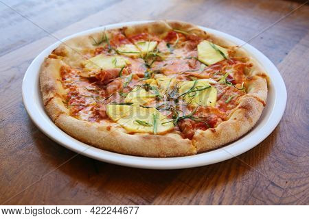 Hawaiian Pizza. A Ham and Pineapple Pizza on a white plate on a wooden table for lunch. Pizza is enjoyed world wide by hungry people.