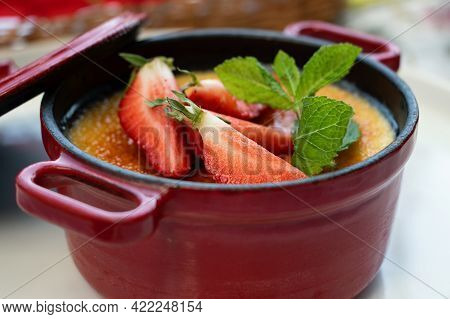 Close Up Photography Of The Dessert Creme Brulee Decorated With Fresh Peppermint And Strawberry.