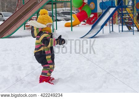 A Child Girl In A Bright Winter Jumpsuit Sculpts A Large Lump Of Snow In The Winter On The Playgroun