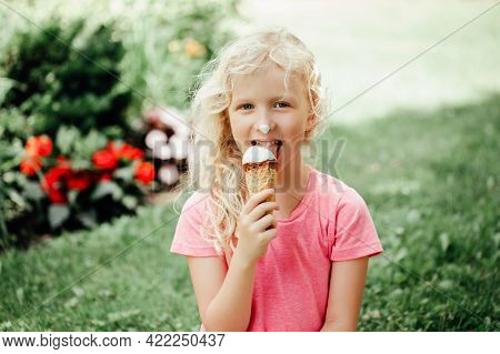 Cute Funny Adorable Girl With Long Messy Blonde Hair Eating Licking Ice Cream From Waffle Cone. Chil