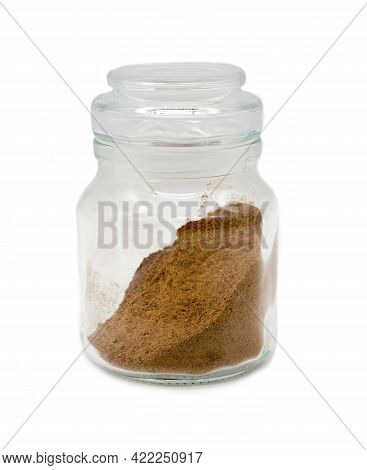 Ground Nutmeg In A Transparent Glass Jar On A White Background.