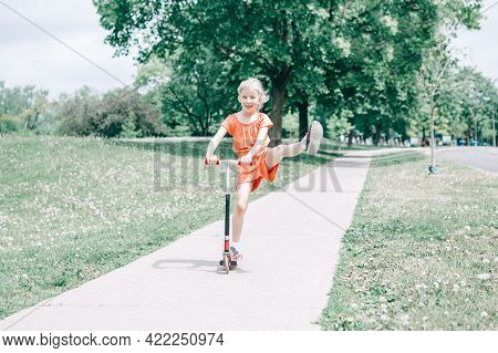Cute Funny Caucasian Girl Child In Red Orange Romper Riding Scooter On Street Road Park Outdoor. Sum