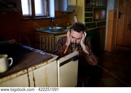 Portrait Of Sad Poor Mature Man Sitting Indoors At Home, Poverty Concept.