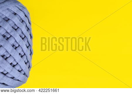 Close-up Of Gray Yarn (knitwear) On A Yellow Background-a Layout Designed For Crocheting.the Concept