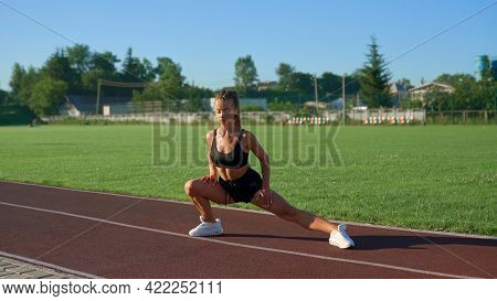Fit Flexible Girl Stretching Legs, Rolling From Side To Side Outdoors. Sexy, Muscular Young Woman Wa