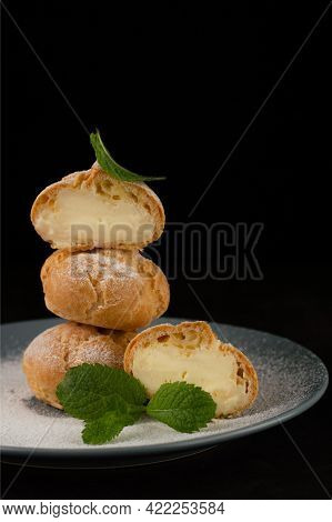 Blurred Image Of Eclairs On A Black Background, Sprinkled With Powdered Sugar With Mint Leaves On A