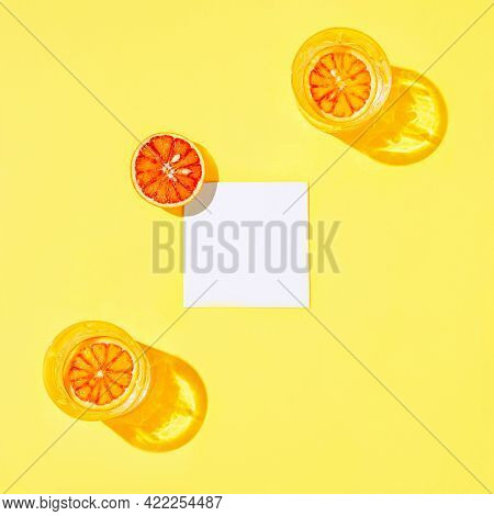 Half Of Bloody Orange With White Paper Card Note And Two Glasse With Water Or Lemonade On Bright Yel