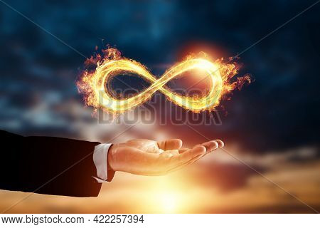 Infinity Fire Sign Over Hand Of Businessman On Sunset Background