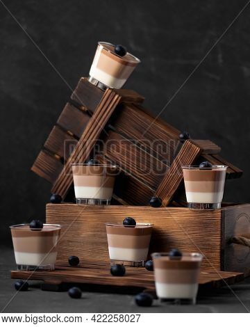 Triple Chocolate Mousse Desserts Or Jelly Decorated With Blueberry In Glass Cup On Black Background.