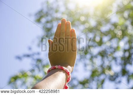 Child's Hand With Handmade Friendship Bracelet Reaches For Blu Sky Concept Of Friendship, Love For N