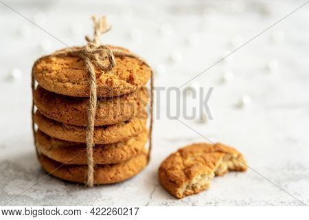 Stacks Of Homemade Oatmeal Cookies With Almonds Tied With A Rope On A Light Background With Bokeh. C