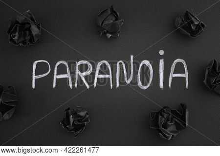 The Word Paranoia On A Black Background With Black Crumpled Paper Balls Around It. Close Up.