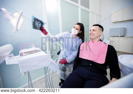 Female Dentist In A Protective Mask And Young Man Sitting In Office And Looking At X-ray. The Dentis