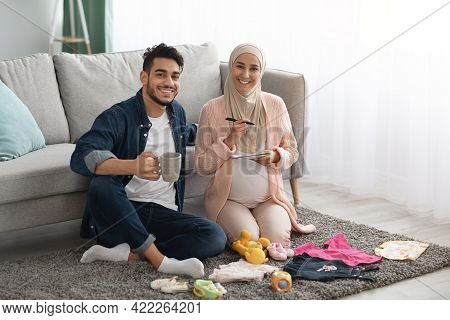 Portrait Of Happy Muslim Couple Making Preparations While Awaiting A Baby