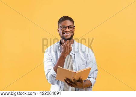 Happy Black Student In Glasses Opening Book For Reading, Studying For Exam On Yellow Background