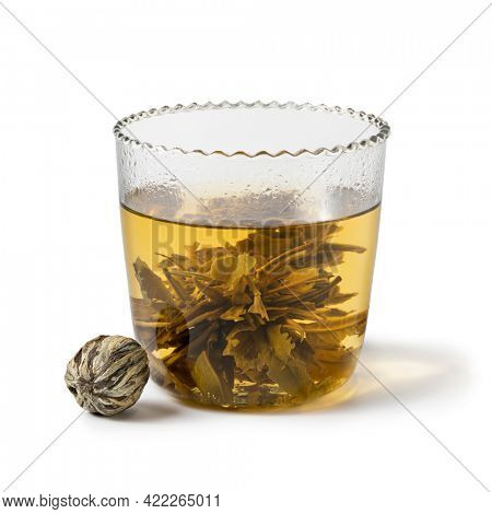 Chinese dried tea pearl growing in a glass tea cup isolated on white background
