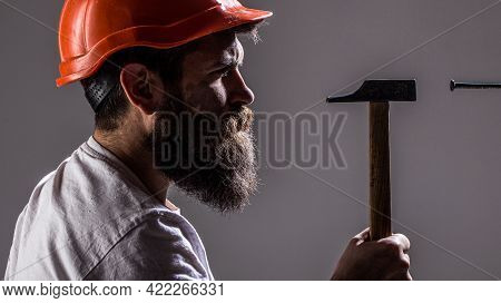 Hammer Hammering A Nail. Handyman Services. Builders In Hard Hat, Helmet. Bearded Man Worker With Be