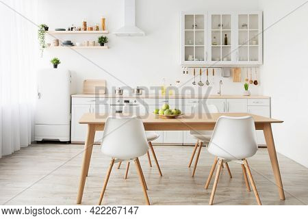 Dining Room And Stylish Design. Wooden Table And White Chairs, Kitchen Utensils On Furniture And Sma