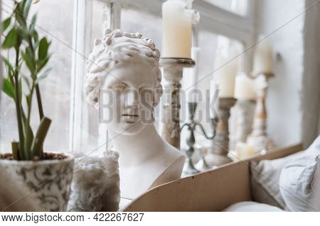Close Up Shot Of Gypsum Venus Head On Windowsill With Antique Candlesticks And Green Potted Plant, B