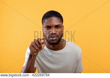 Concept. African American Man Gazing And Pointing Finger At Camera, Standig Over Yellow Background