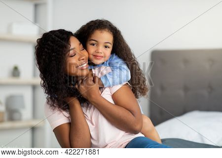 Maternal Love. Cheerful Black Girl Hugging Her Mommy On Bed At Home
