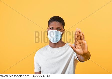 Stop Covid-19. Black Guy Wearing Protective Face Mask And Gesturing Stop To Camera, Standing Over Ye
