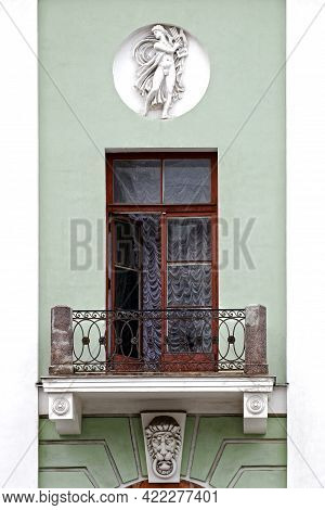 Balcony With A Cast-iron Fence And Stucco Molding, With An Open Balcony Door Against The Background