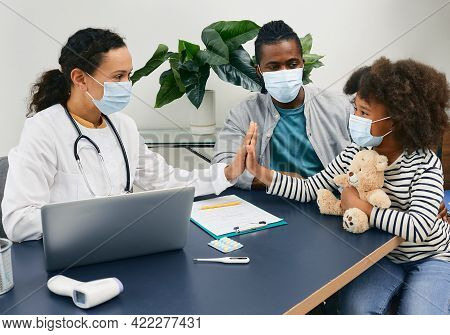 Pediatrician Consultation. African American Girl With Her Daddy Wearing Protective Masks At The Doct