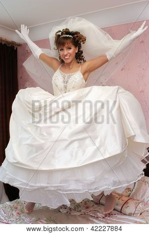 Happy Bride is jumping on her bad in wedding dress poster