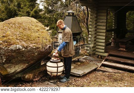 Young Man In A Country Dacha Prepares Meat On The Grill.