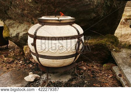 Tandoor Cylindrical Clay Or Metal Oven. Burning Wood Inside The Stove.