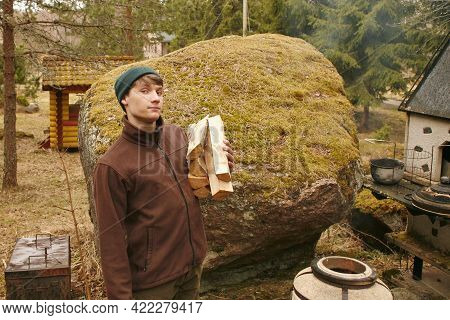 Young Man Carries Firewood For Tandoor. Tandoor Cylindrical Clay Or Metal Oven Used In Cooking.