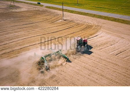 Aerial View. Tractor Plowing Field. Beginning Of Agricultural Spring Season. Cultivator Pulled By A
