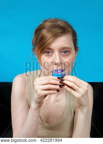 Young Woman Holding Blue Led Lamp Inside Mouth While Whitening Teeth At Home