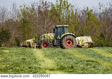 Papa, Hungary - May 10, 2021: Claas Tractor Working On Meadow. Agriculture Industry And Business. Ve
