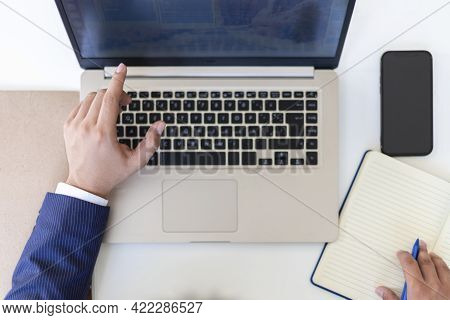 Flat Lay, Hand Of Businessman Writing On Notebook With Laptop Computer And Cellphone, Binder And Pen