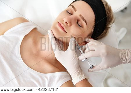 Doctor-cosmetologist Making Beauty Injection On The Face Of A Young Woman At Spa Center. Concept Of