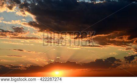 Shiny Golden Sun Rays Break Through Dark Clouds. Orange Color Cloudscape Of Sunset. Dramatic Sky Whi