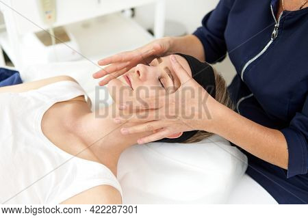 Esthetician Performing Professional Facial Massage On Woman Face At Spa Clinic. Face Lifting Anti-ag