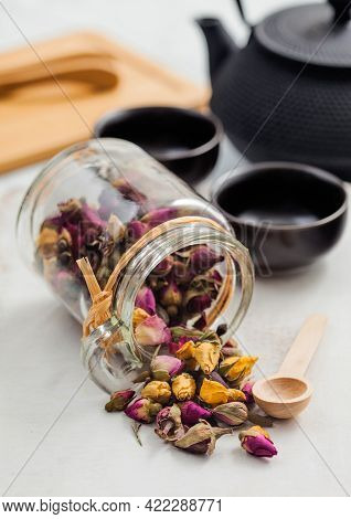Glass Jar Of Rose Buds Mix Tea With Wooden Scoop On White Background With Black Iron Teapot And Cups