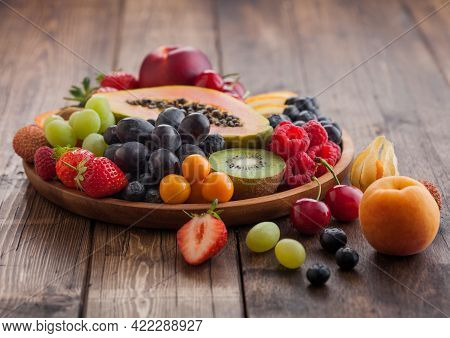 Fresh Raw Organic Summer Berries And Exotic Fruits In Round Wooden Plate On Light Wooden Kitchen Bac