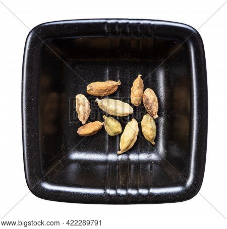 Top View Of Several Cardamom Pods In Black Bowl Isolated On White Background