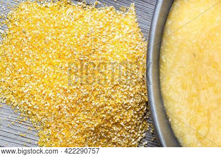 Top View Of Pile Of Cornmeal And Cooked Maize Porridge In Gray Bowl On Gray Wooden Table