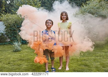Beautiful Girl And Boy Play With Orange Colored Smoke. They Look At The Camera.
