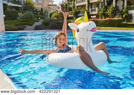 A Happy Girl In An Inflatable Circle In The Form Of A Unicorn Swims In A Pool