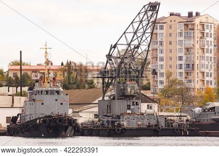Sevastopol. Crimea. Winter 2021. Crane And Tug In The Bay. A Large Tug And A Floating Crane Stand Ag