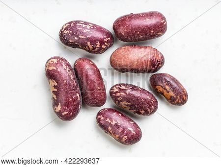 Several Raw Red Spotted Pinto Beans Close Up On Gray Ceramic Plate